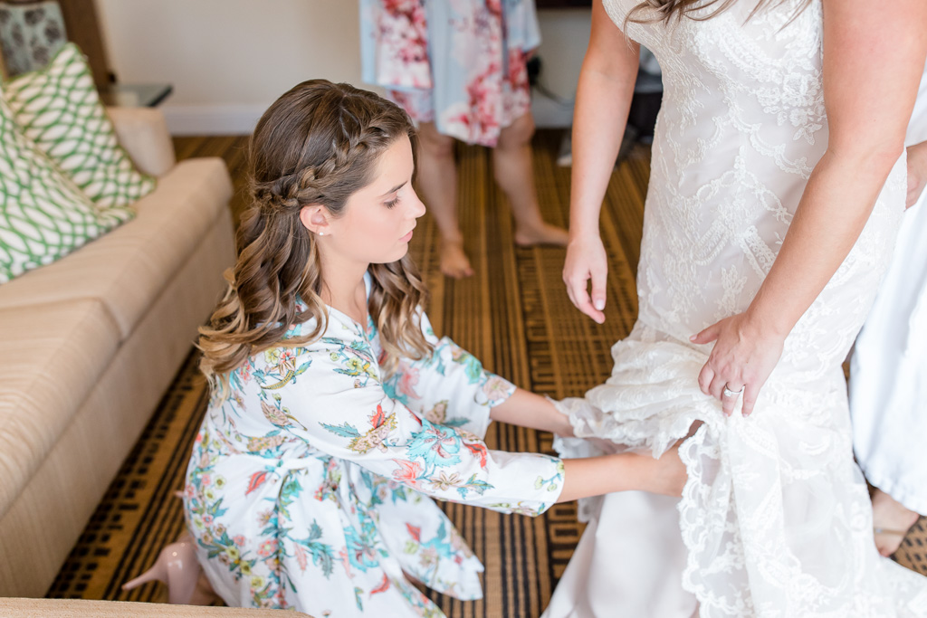 junior bridesmaid in her floral robe helping bride getting into her dress