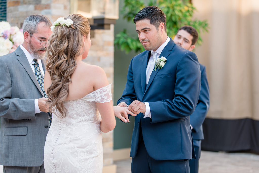 groom putting the ring on bride's finger