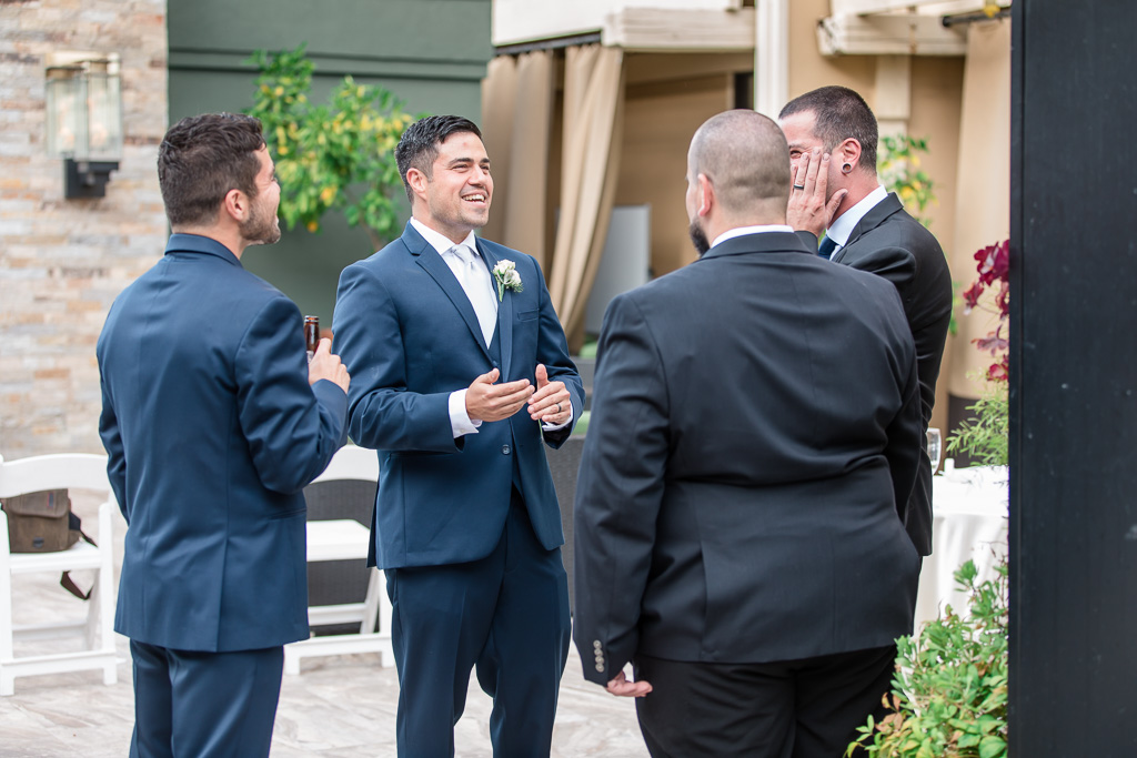 groom chatting with friends during cocktail hour