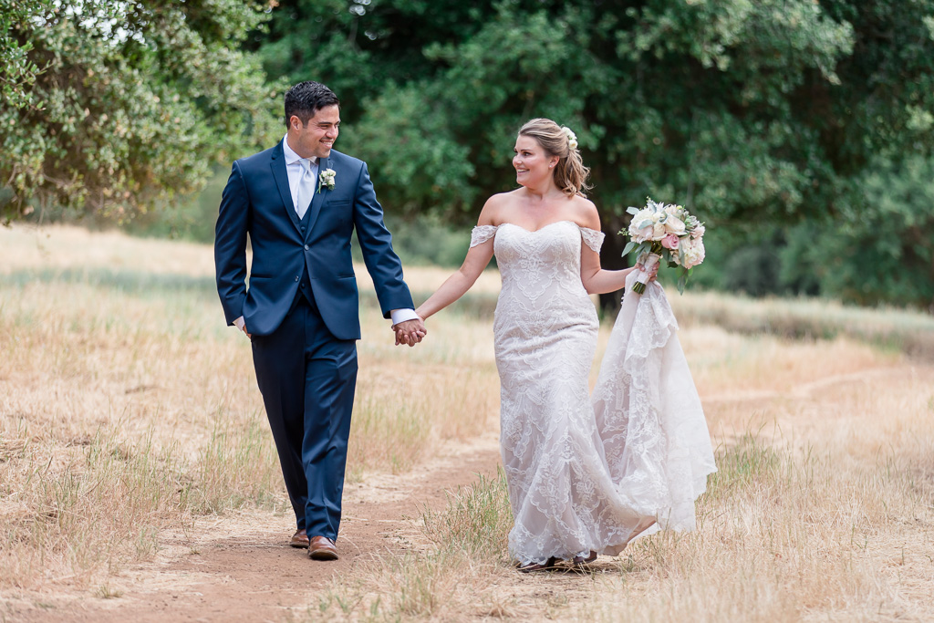 newlyweds walking on a grassy path