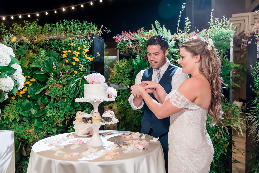 cake cutting in front of a flower wall