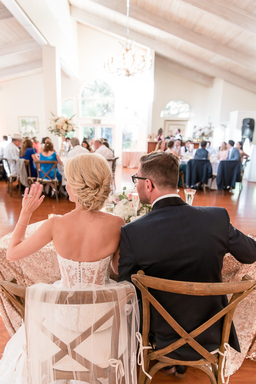 couple waving at guests from their sweetheart table