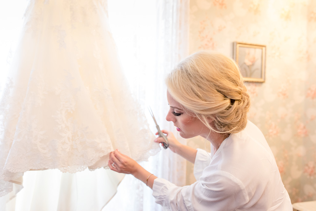 bride adding final details to her wedding dress