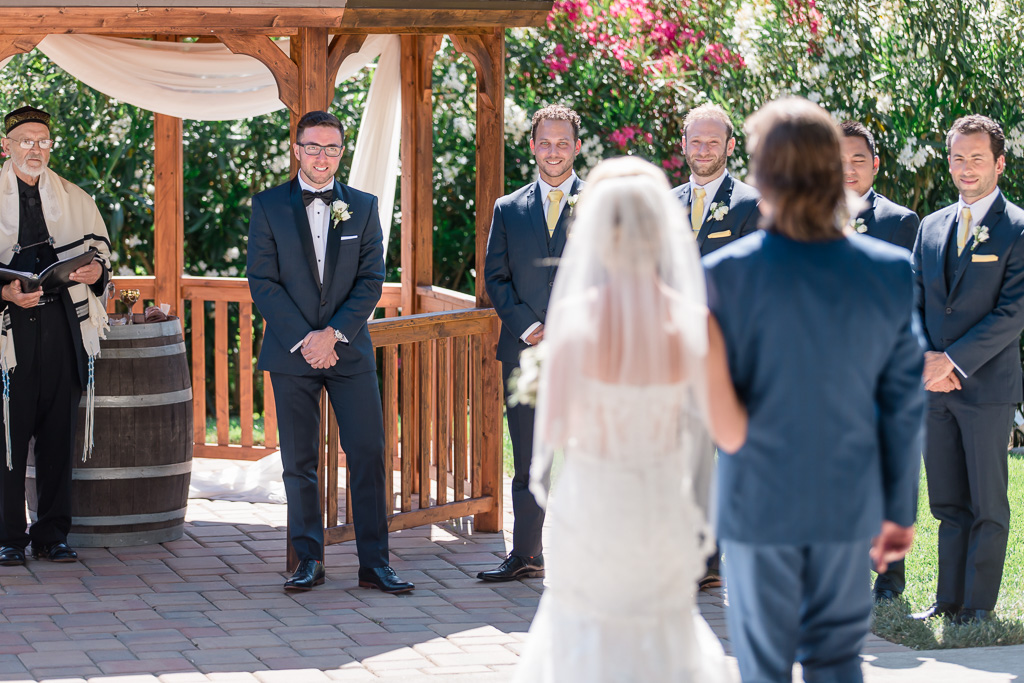 groom is so happy to see his bride walking down the aisle