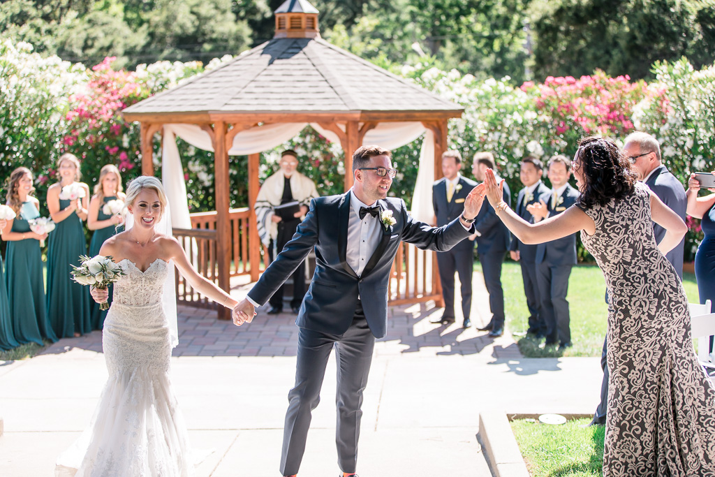 high five with wedding guests during ceremony recessional