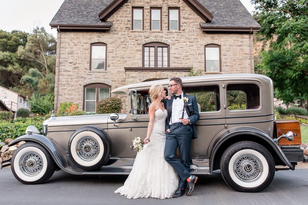 newlyweds with their classic car in front of the elliston mansion
