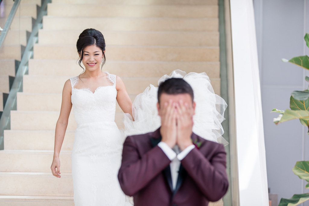 bride walking down hotel staircase for their first look