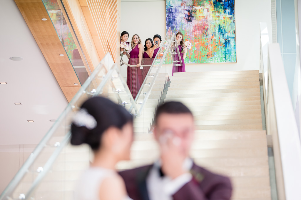 bridesmaids peeking the first look from above the staircase