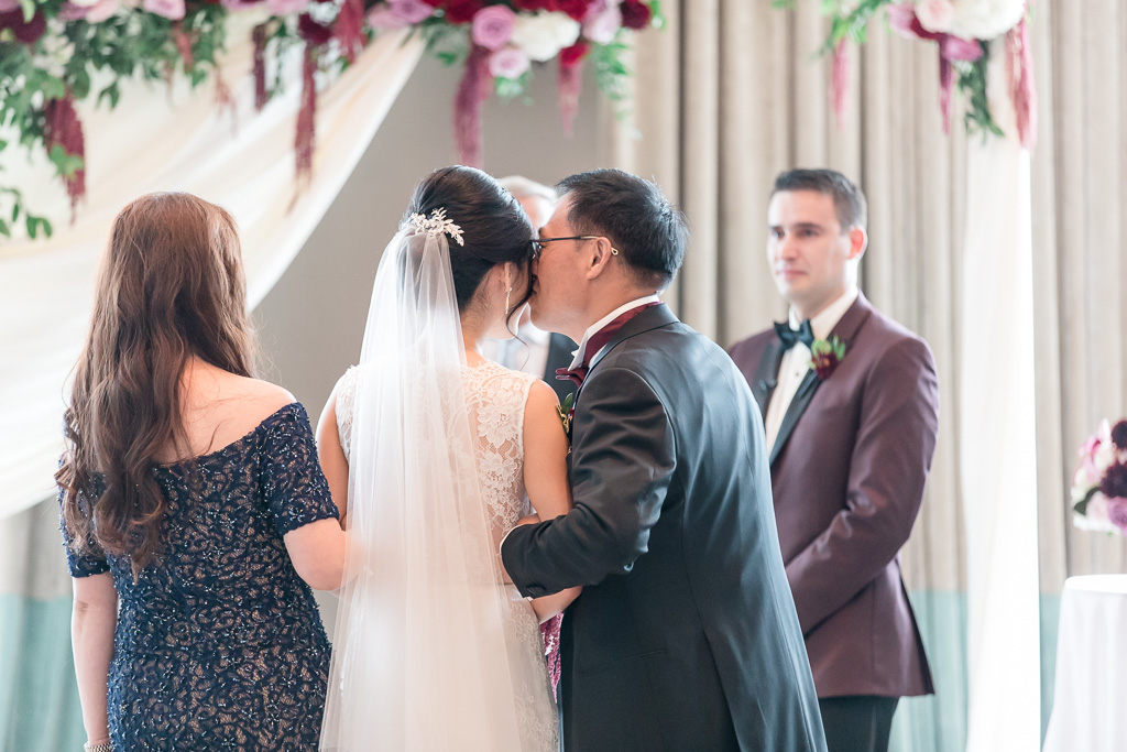father of the bride giving her a kiss on the forehead at the end of the aisle