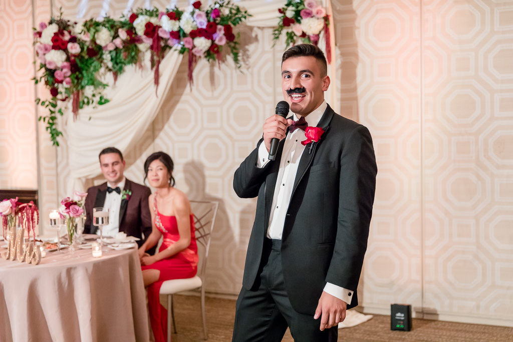 best man with a fake mustache giving a toast