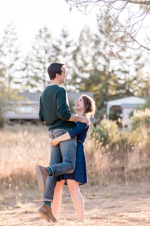 she lifted him up in the air for their engagement photo