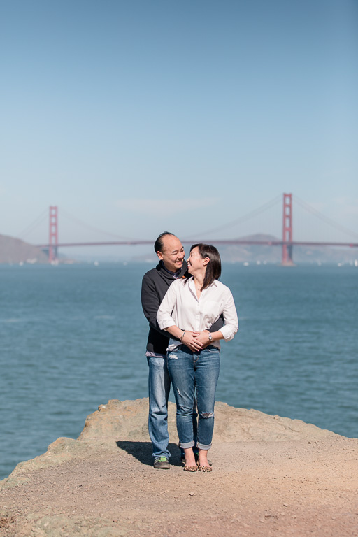 engaged couple at lands end by the golden gate bridge
