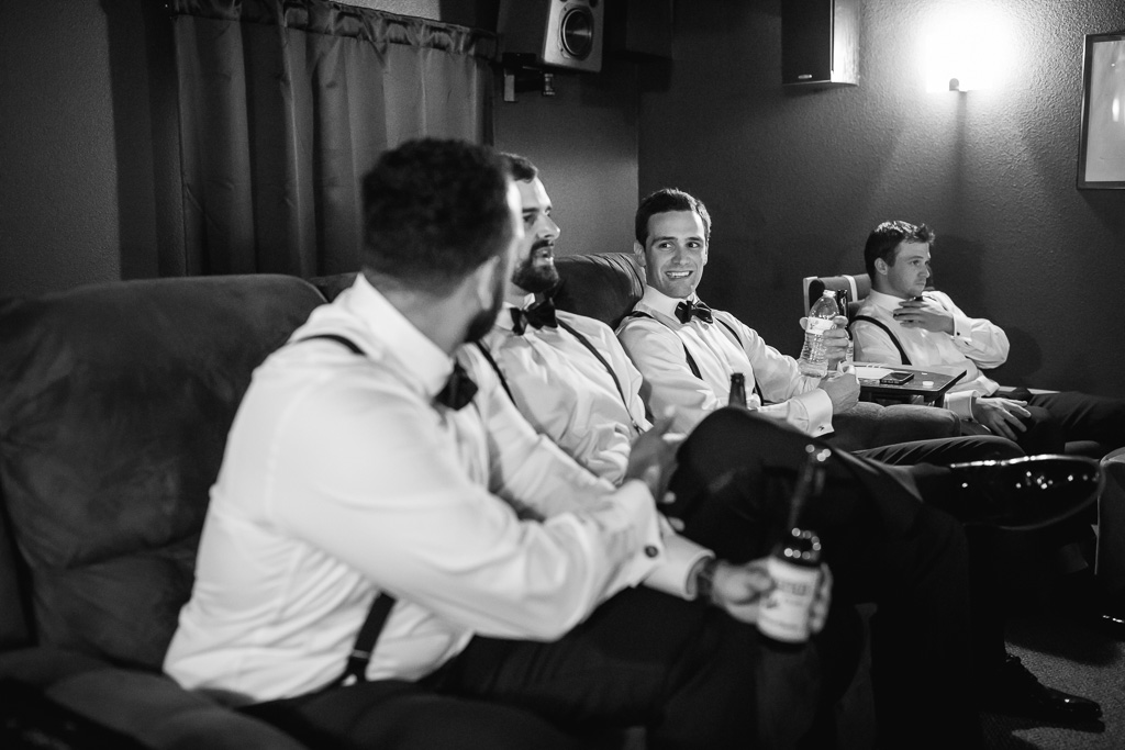 groom and groomsmen watching football when getting ready