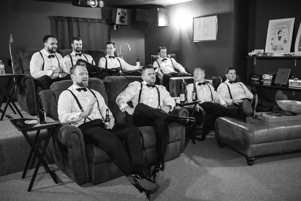 groom and groomsmen chilling at the theater room at the highlands estate