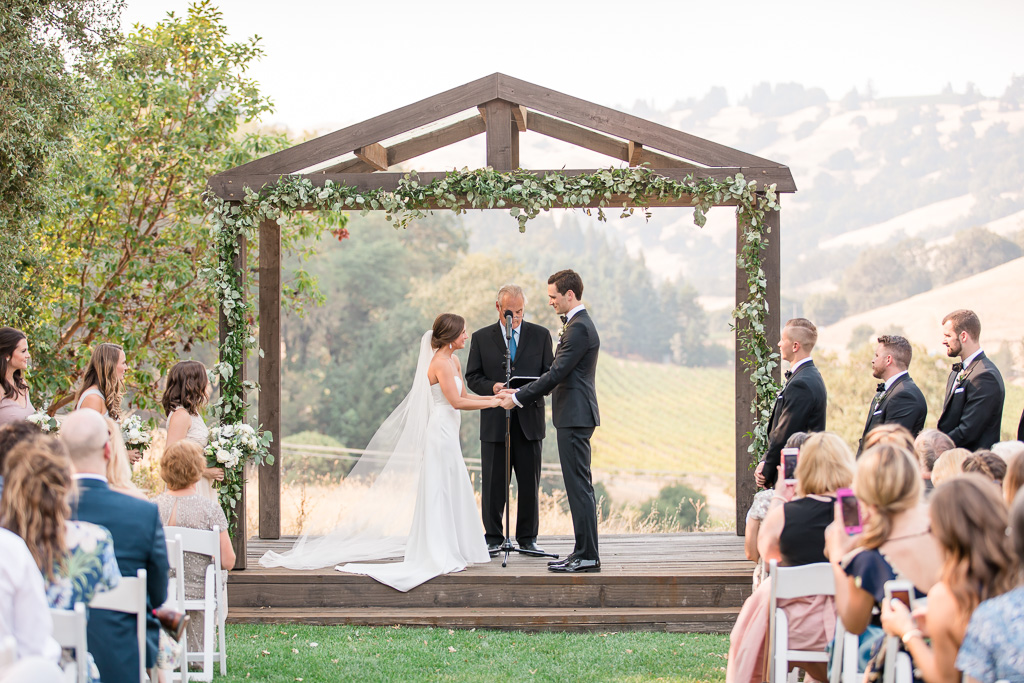 a beautiful wedding ceremony under the wooden gazebo at the highlands estate in cloverdale