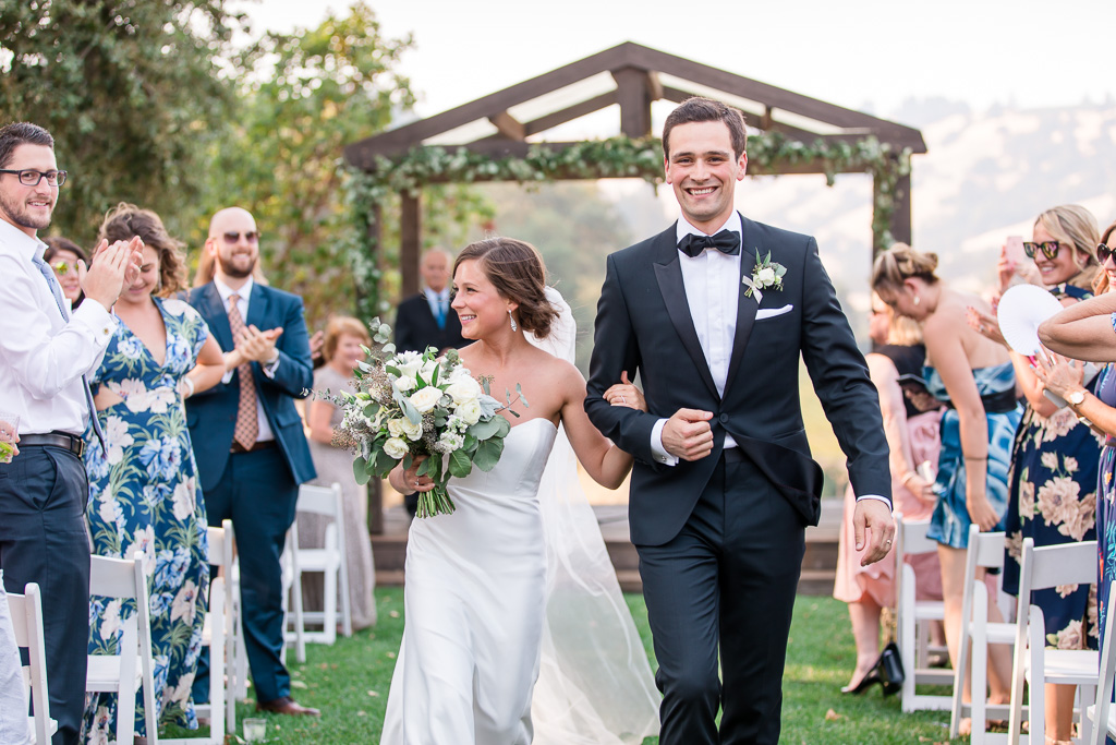 happy newlyweds walking down the aisle at the highlands estate
