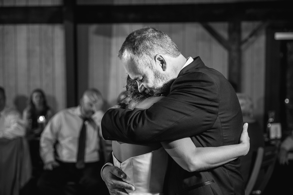 an emotional hug between the bride and her father