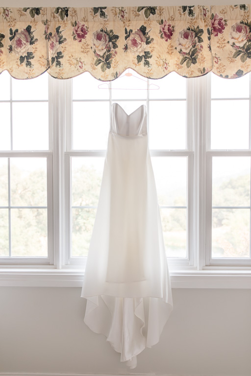 elegant and simple wedding dress hanging on the big windows