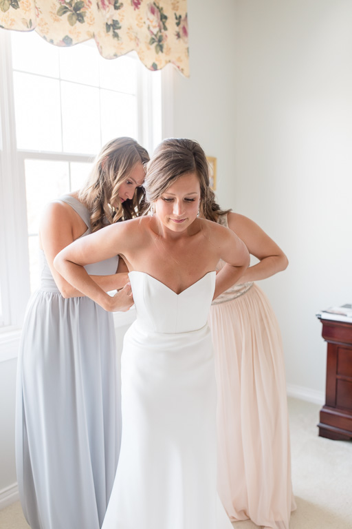 bridesmaids zipping up the wedding dress for the bride