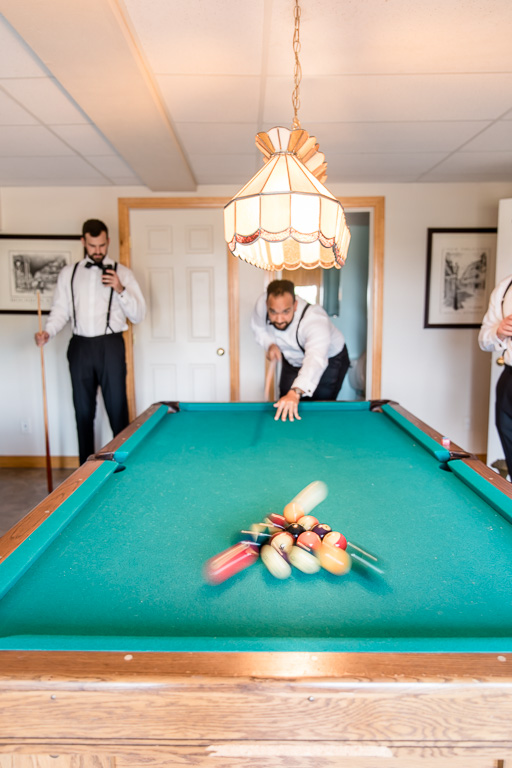 groomsmen and groom playing pool when getting ready