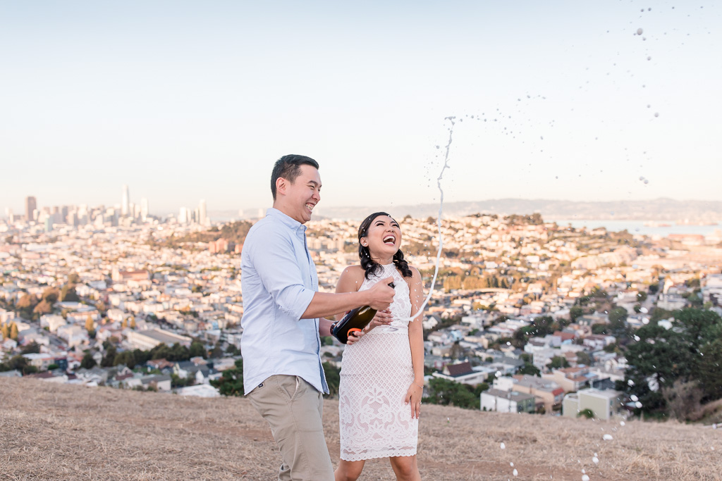 having fun uncorking champagne at engagement session