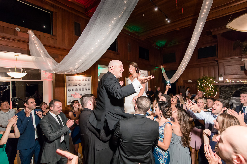 wedding guests lifting bride and groom up