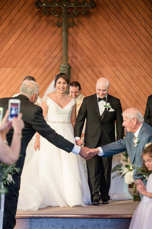 fathers shaking hands as newlyweds walk down the aisle as husband and wife