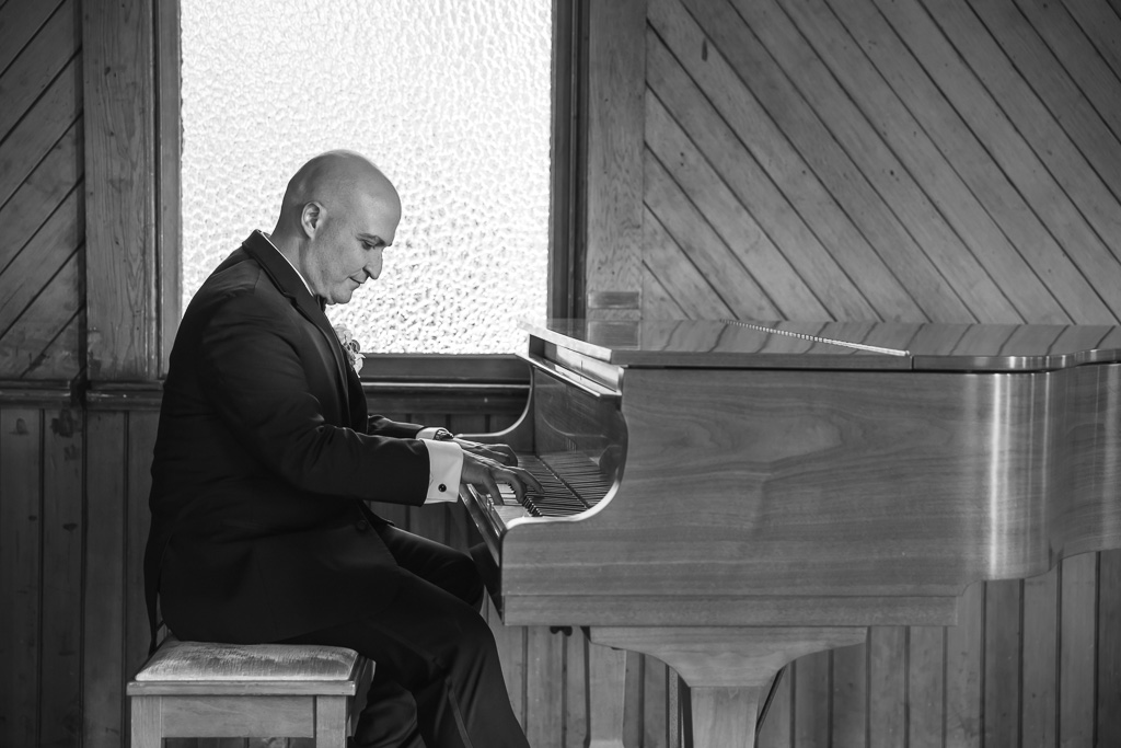groom playing piano at the church