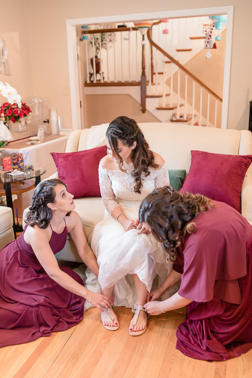 sisters helping the bride with her shoes