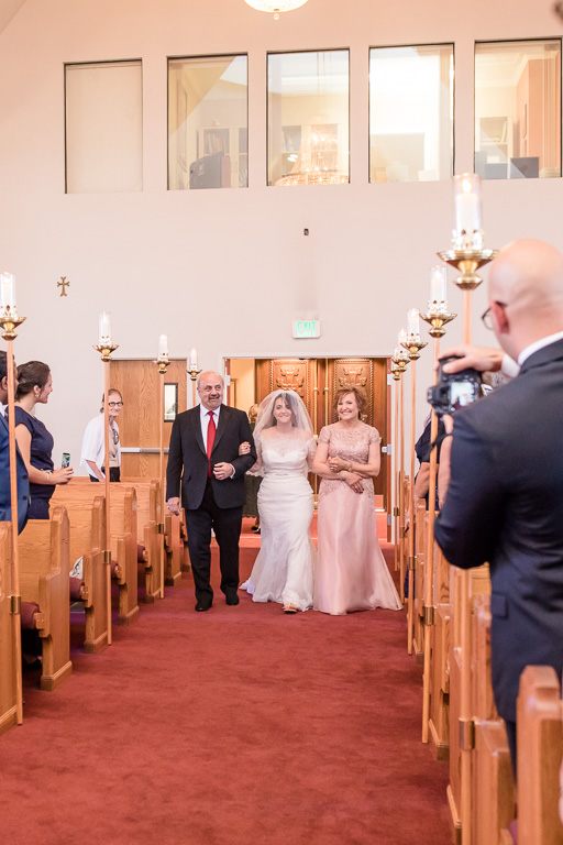 bride walking down the aisle escorted by parents