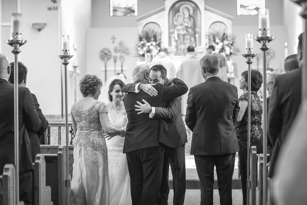 newlyweds hugging their parents before walking down the aisle as husband and wife