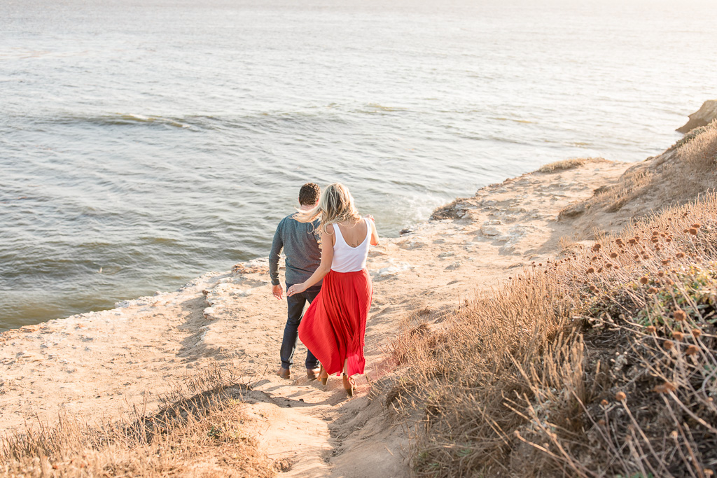 candid walking engagement photo by pacific ocean