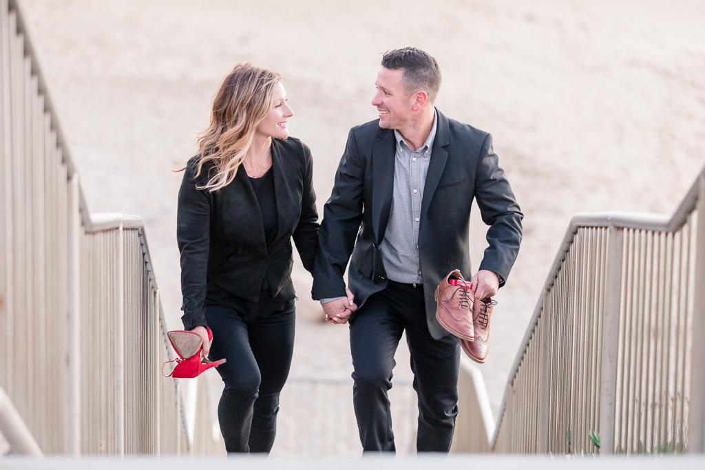 cute couple walking up steps from beach