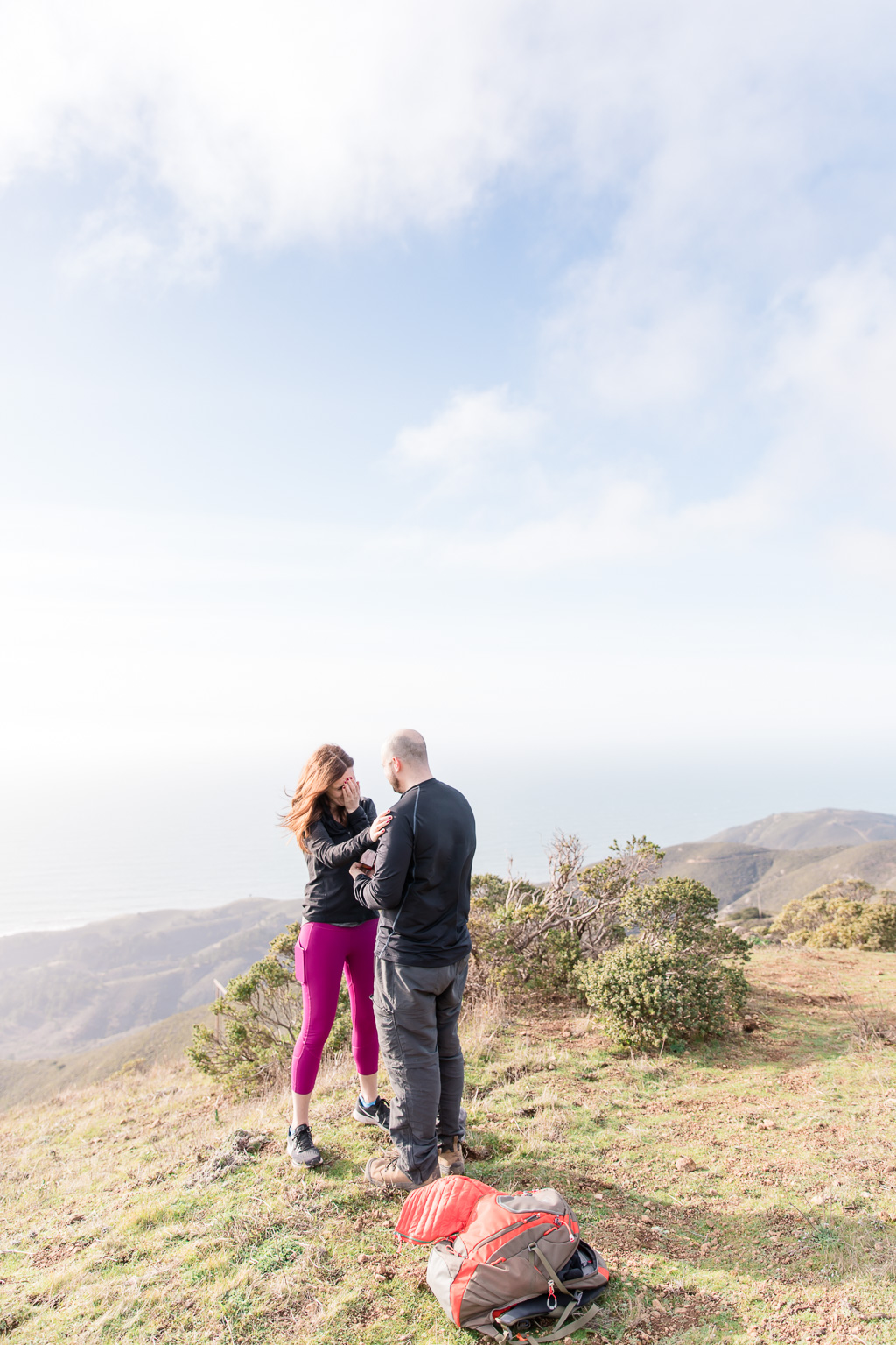 Surprise engagement captured by professional photographers on top of the mountains