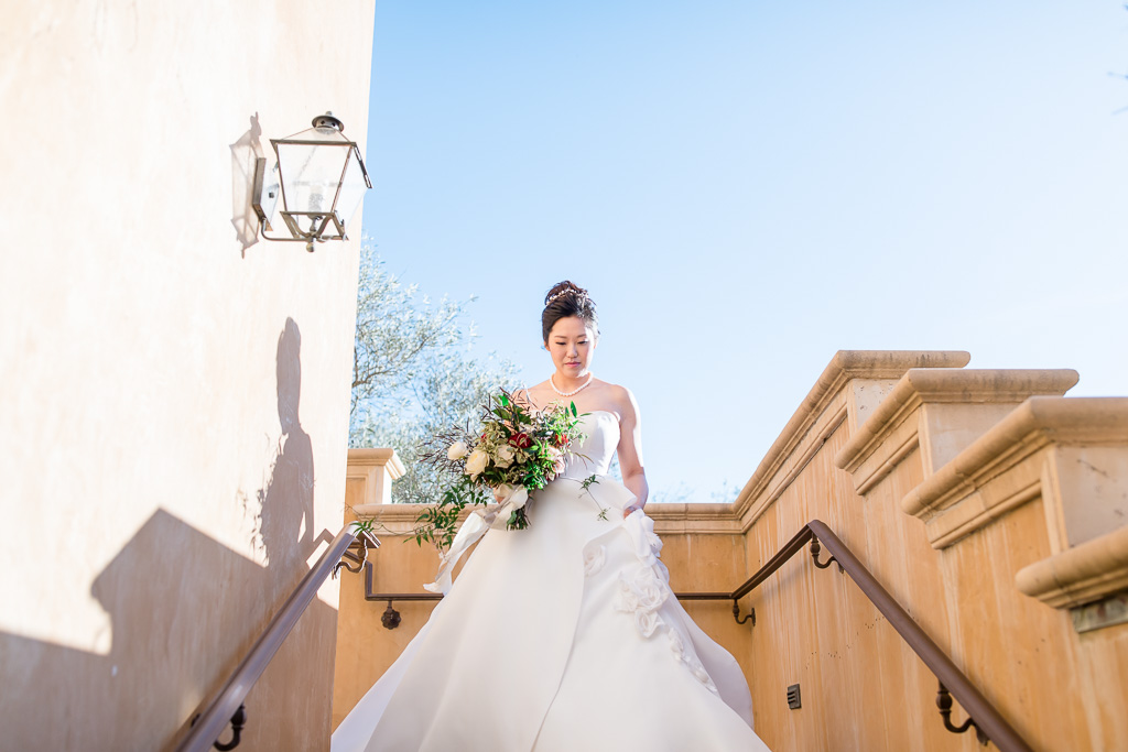 candid photo of the bride walking down the staircase to meet her groom
