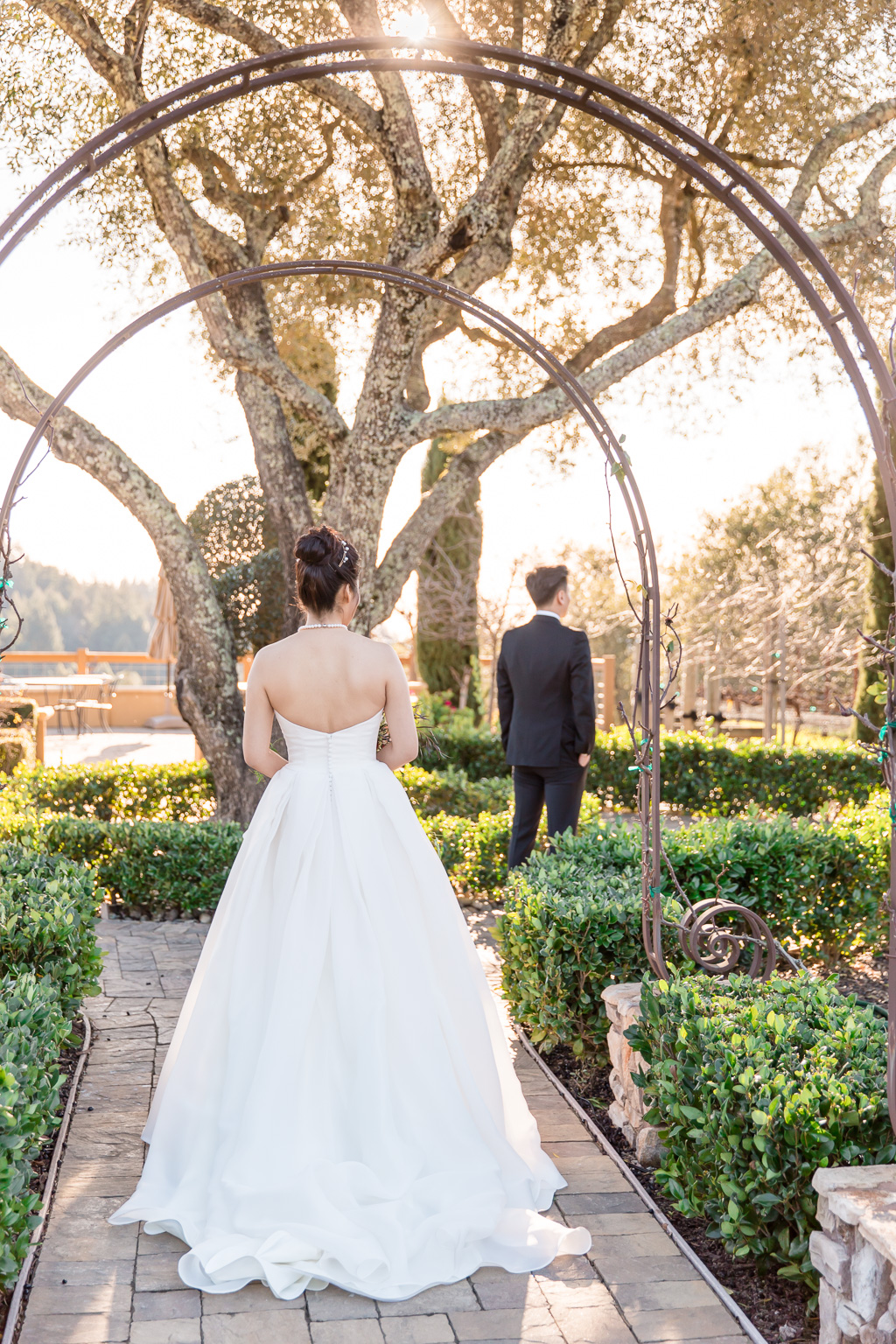bride walking toward her groom for the first look near the regale olive tree
