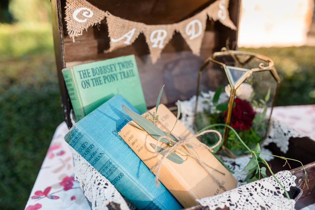 wedding sign in table suitcase with vintage books and flowers