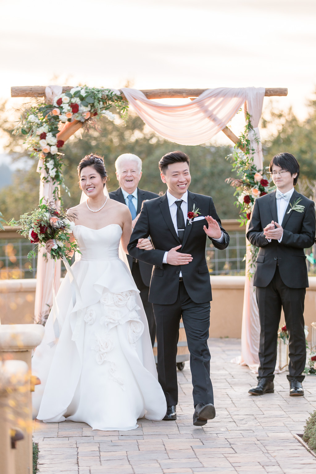 waving at their guests at the end of the ceremony