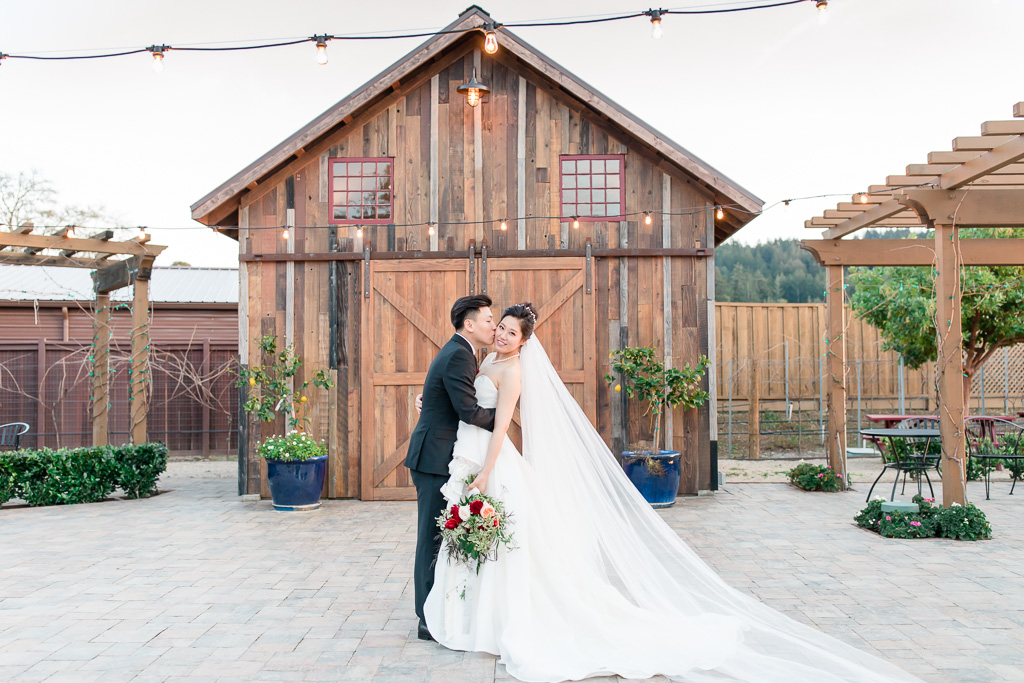 bride and groom in front of the regale winery barn