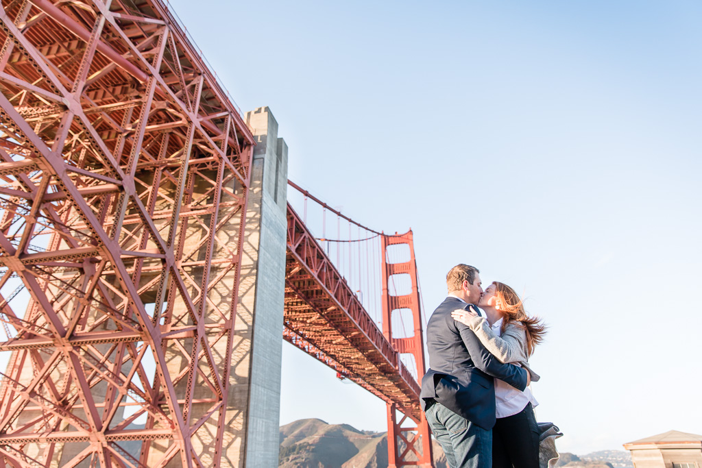 couple portrait taken at a different angle from below the golden gate bridge