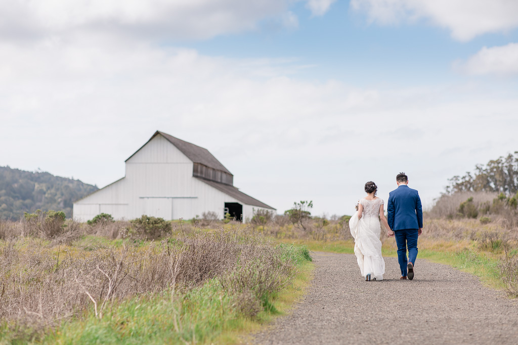 newlyweds walking towards a cute barn
