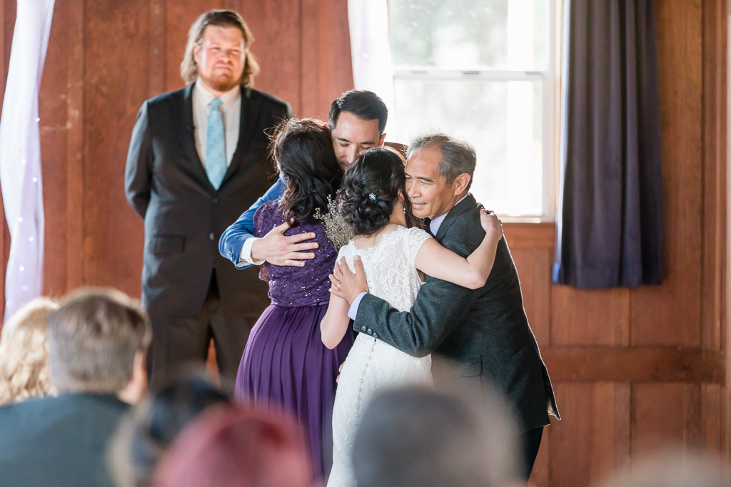 bride and groom hugging their parents