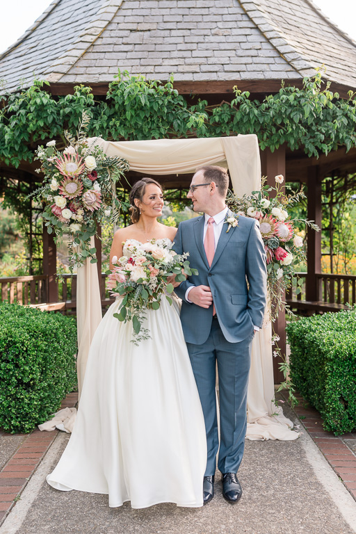bride and groom standing in front of their beautifully decorated chuppah