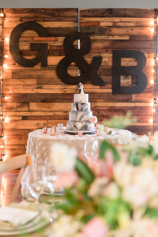 pretty marble wedding cake presentation in front of a huge customized wooden backdrop