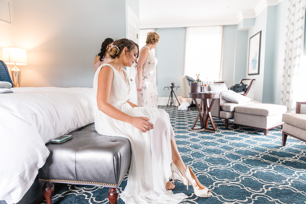 bride getting into her shoes in the suite