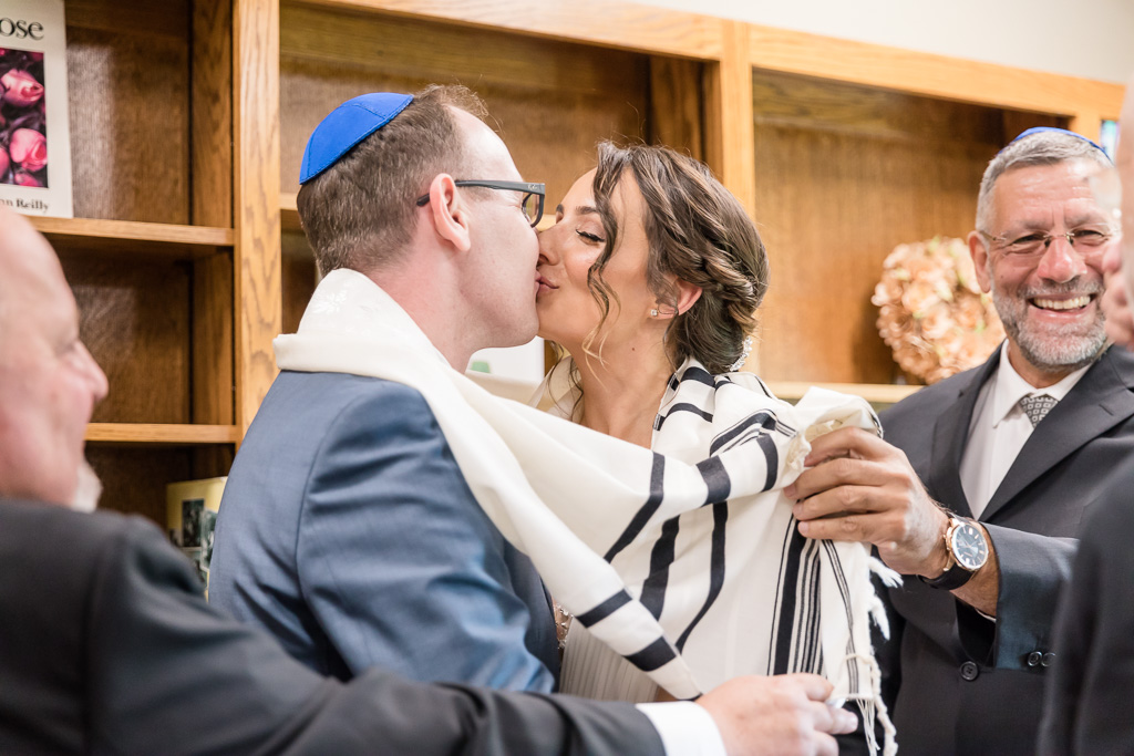 couple kissing at the end of the ketubah signing