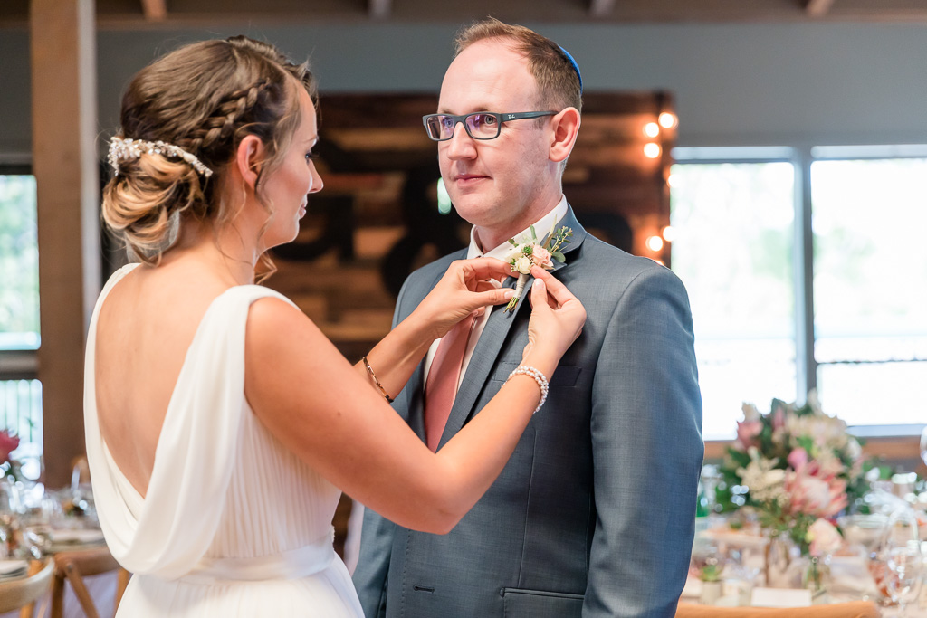 bride pinning the boutonniere for the groom
