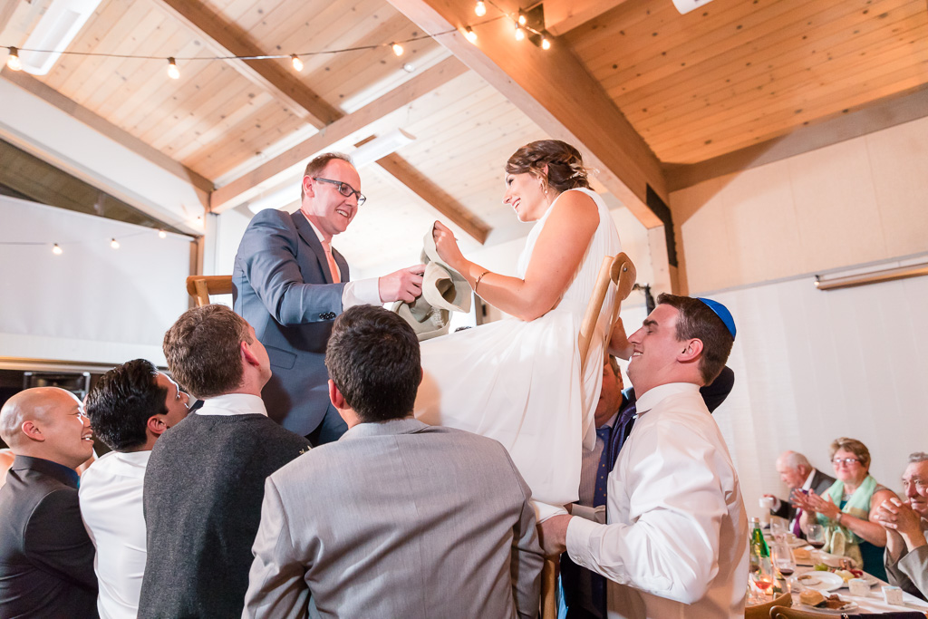 Bride and groom being lifted up in their chairs - Jewish Hora dance