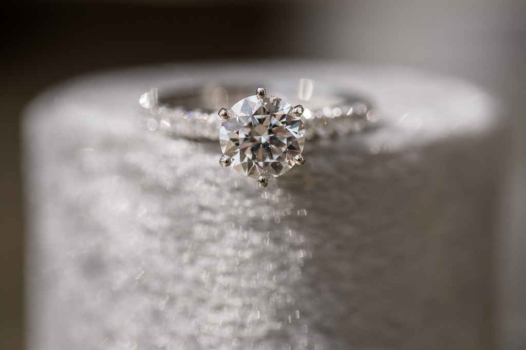 soft macro photo of diamond ring on round gray velvet box