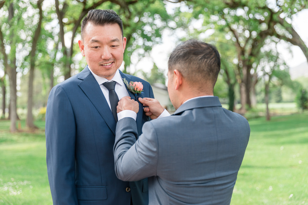 groomsman helping groom with his boutonnière